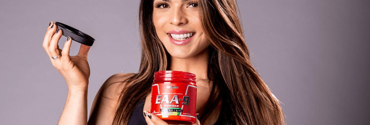 mulher sorrindo e segurando pote vermelho de aminoacidos essenciais